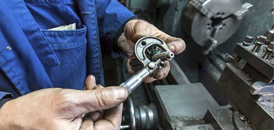 Man-setting-up-his-lathe-cutting-tools