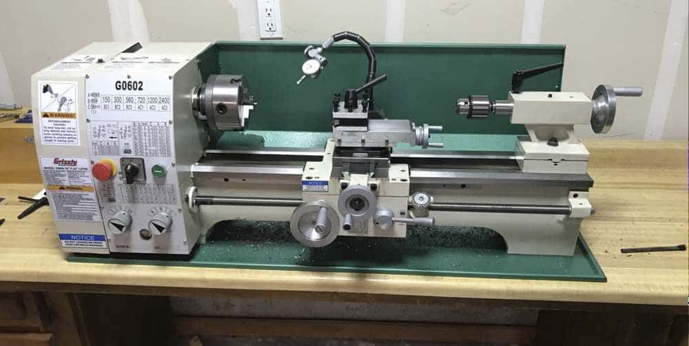 """""""a green colored grizzly G0602 metal lathe on a wooden benchtop"""""""
