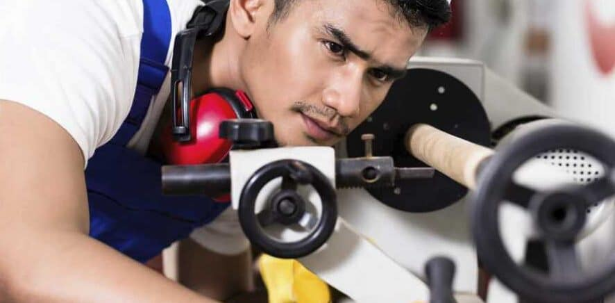 """Man wearing white and blue t-shirt is checking a white mini wood lathe during work"""