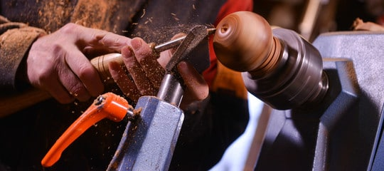 """""""Man's hand with a chisel turning small door knob on a wood lathe"""""""