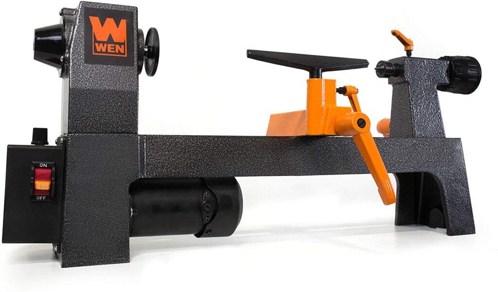 """Black body with orange tool rest, Wen-3421 mini wood lathe in a white background"""